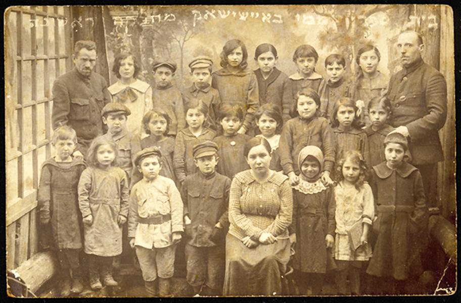 Pirma Hebrajų dienos mokyklos klasė kartu su trimis mokytojais: Moshe Yaakov Botwinik (dešinėje), Yaakov Schneider (kairėje), Rivka Rubinstein (centre). 1930 m.